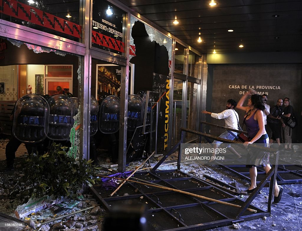 Demonstrators vandalize the Casa de Tucuman and clash with riot police in Buenos Aires, on December 12, 2012 during a protest against the sentemce that allowed the release of 13 indicted in cases of forced disappearance of women, prostitution and involvement in the case of Marta Veron, disappeared in the province of Tucuman ten years ago.