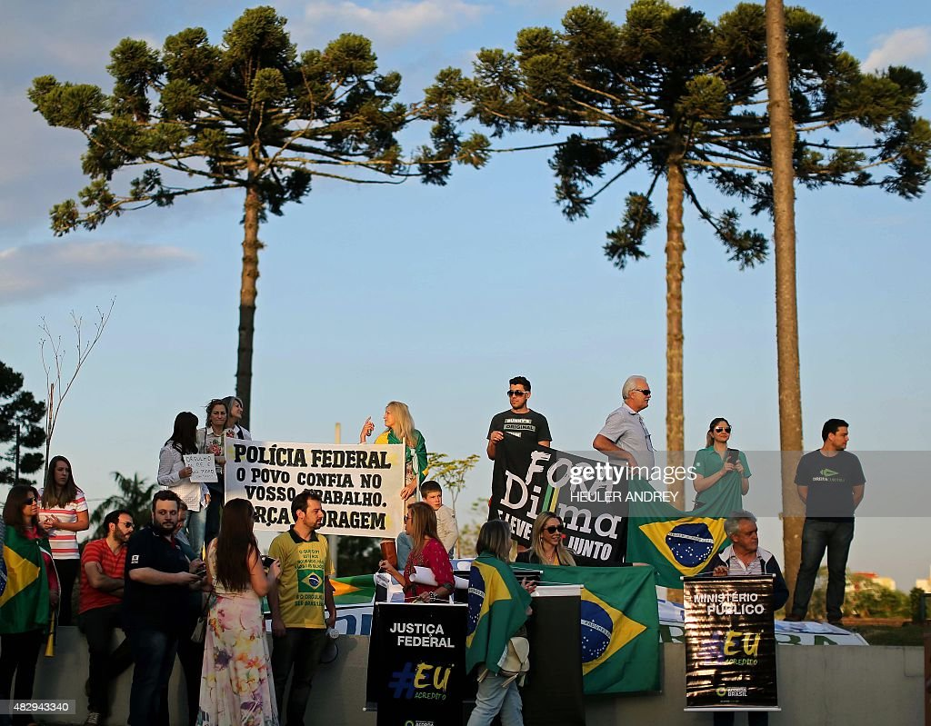 Demonstrators wait with banners outside the Federal Police headquarters in Curitiba Brazil on August 4 as Brazilian former chief of staff Jose Dirceu...