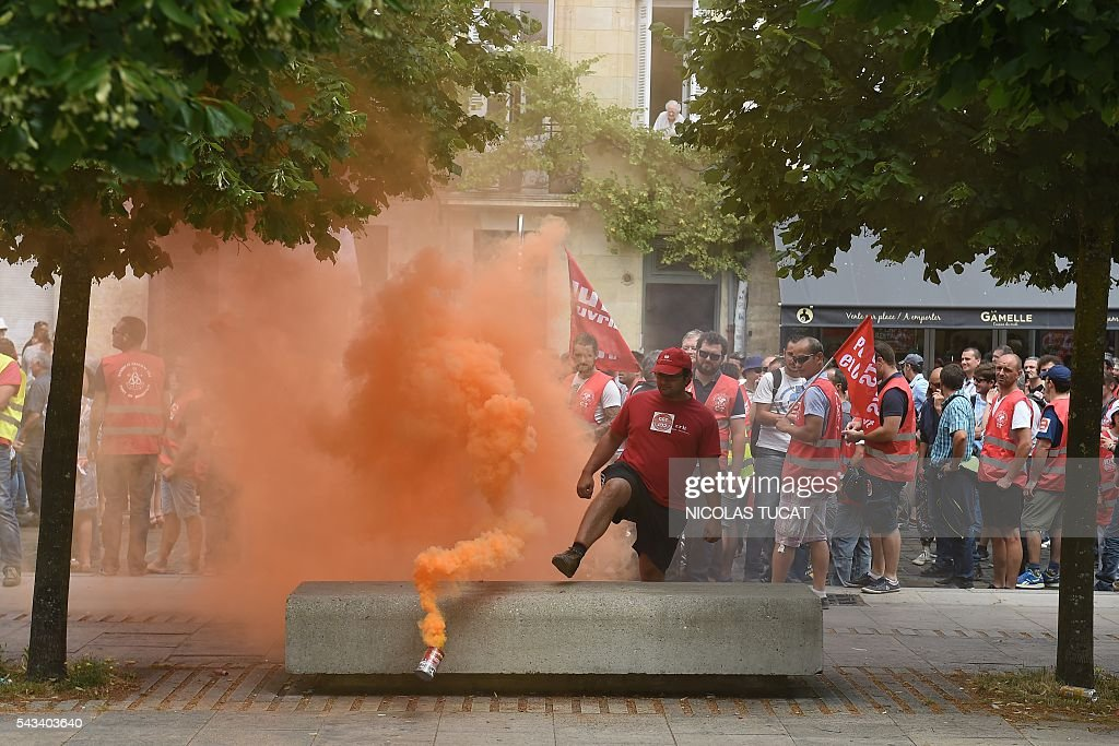 Demonstrators walk in an orange smoke cloud during a demonstration against proposed labour law reforms in Bordeaux on June 28, 2016. Unions have called repeated strikes and marches against controversial labour reforms, forced through by the government of Socialist President Francois Hollande. / AFP / NICOLAS
