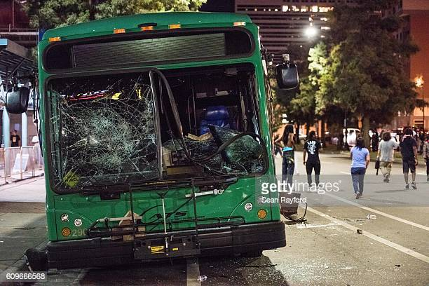Demonstrators walk near a damaged bus on September 22 2016 in downtown Charlotte NC The North Carolina governor has declared a state of emergency in...
