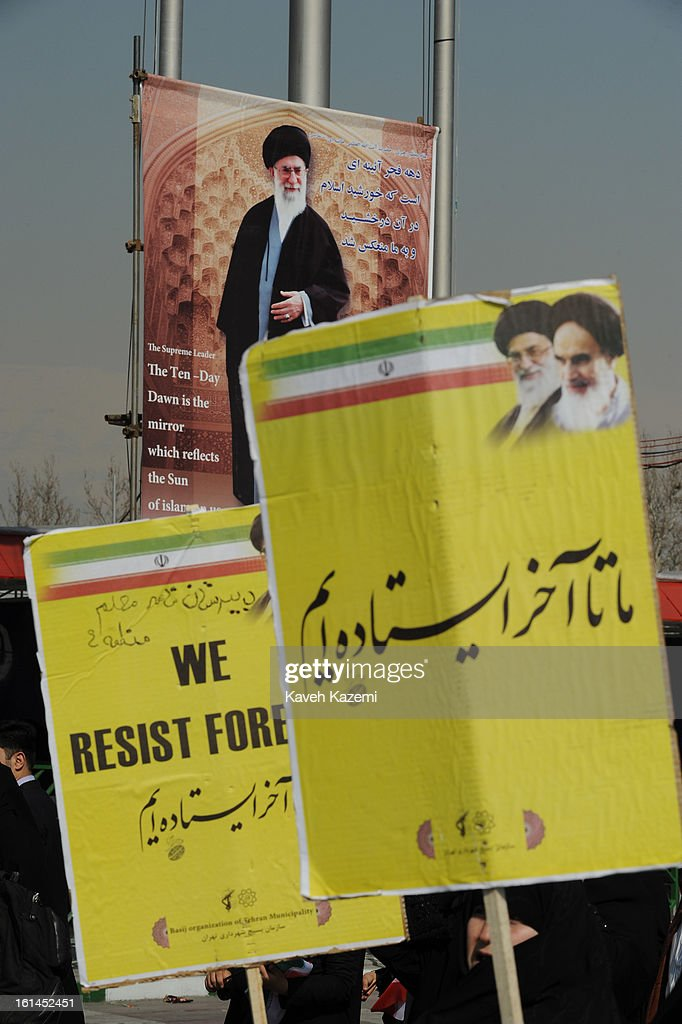 Demonstrators walk past a large banner of Ayatollah Ali Khamenei carrying small banners reading 'We Resist Forever' during the 34th anniversary of the Islamic revolution in Azadi square on February 10, 2013 in Tehran, Iran.