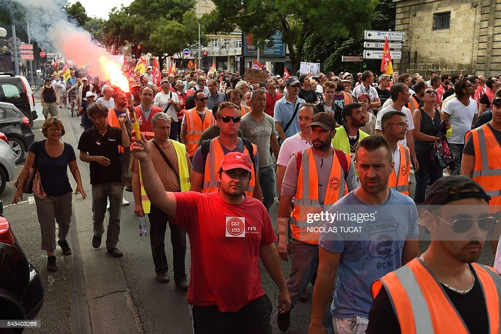Demonstrators walk with flares during a demonstration against proposed labour law reforms in Bordeaux on June 28, 2016. Unions have called repeated strikes and marches against controversial labour reforms, forced through by the government of Socialist President Francois Hollande. / AFP / NICOLAS