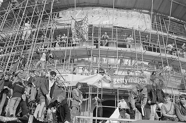 Demonstrators watch from the safety of a scaffolded building as rioters clash with police in Trafalgar Square during violence which arose from a...