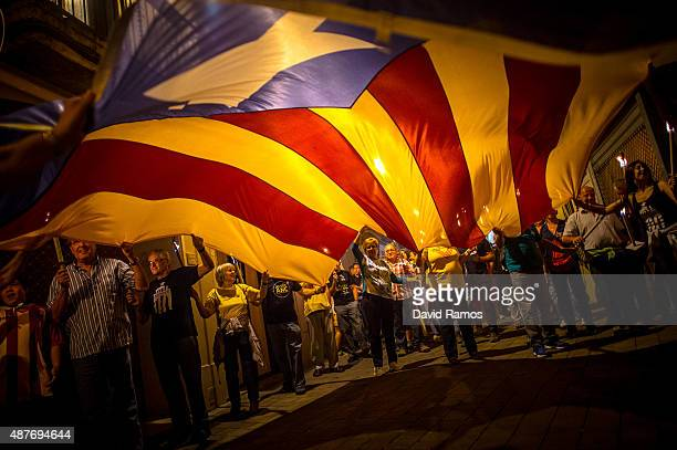 Demonstrators wave a huge ProIndependece Catalan flag as they march during a Catalan ProIndependence demonstration on September 10 2015 in Vilafranca...