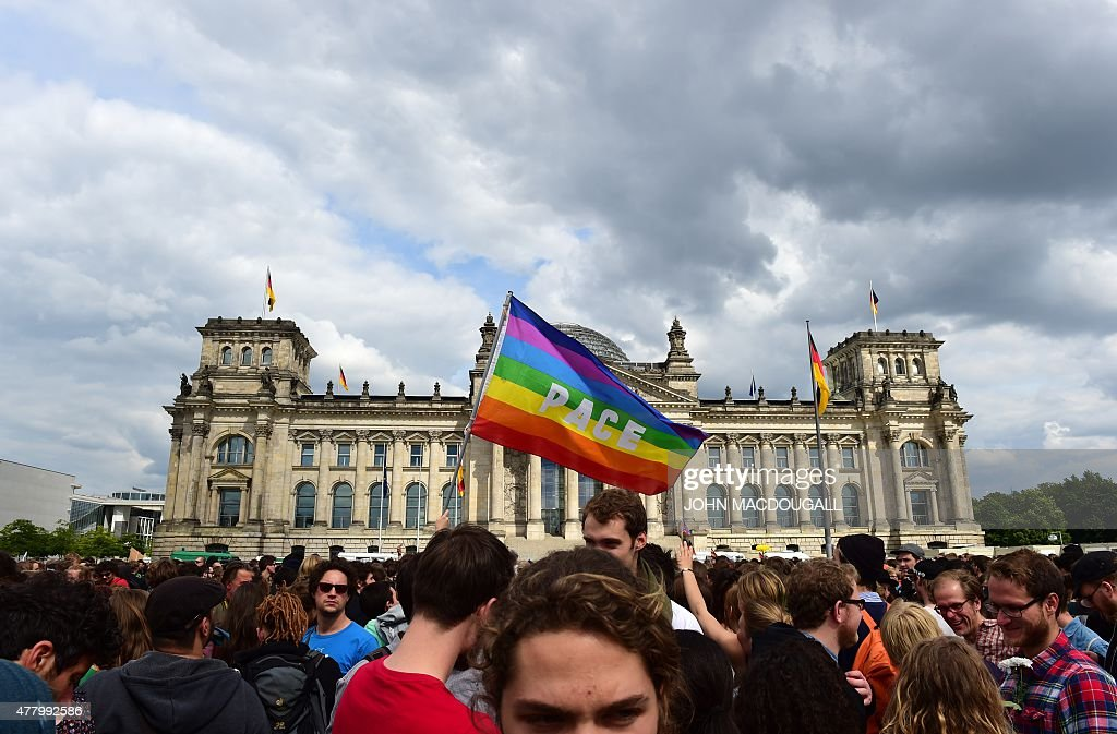 Demonstrators wave a Peace flag as they protest for the rights of immigrants and refugees in front of the Reichtsag building housing the Bundestag...