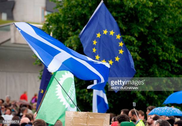 Demonstrators wave EU and Scottish Saltire flags at a protest by Pro EU campaigners outside the Scottish Parliament ahead of a debate on the EU...