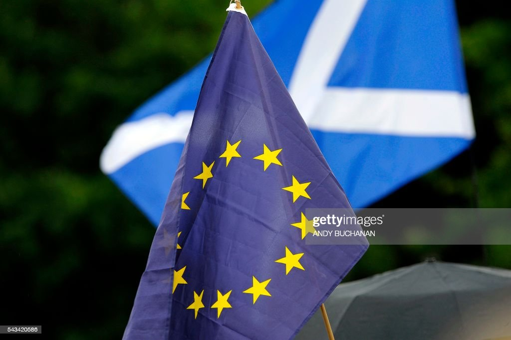 Demonstrators wave EU and Scottish Saltire flags at a protest by Pro EU campaigners outside the Scottish Parliament ahead of a debate on the EU Referendum result and the implications for Scotland, in Edinburgh, Scotland on June 28, 2016. Scottish First Minister Nicola Sturgeon said she would travel to Brussels on Wednesday for talks to defend Scotland's place in the European Union after a vote by Britain as a whole to leave the bloc. Sturgeon said she was 'utterly determined' to protect Scotland as she asked an emergency session of the Scottish parliament on Tuesday for a formal mandate for direct talks with the European Union institutions. / AFP / Andy Buchanan