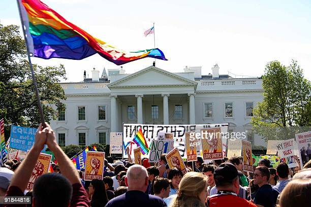 Demonstrators wave flags and banners in front of the White House in Washington on October 11 2009 as tens of thousands of gay activists marched to...