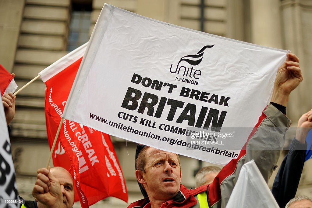 Demonstrators wave flags during a protest in central London on October 19 2010 Thousands of demonstrators rallied in London Tuesday against harsh...