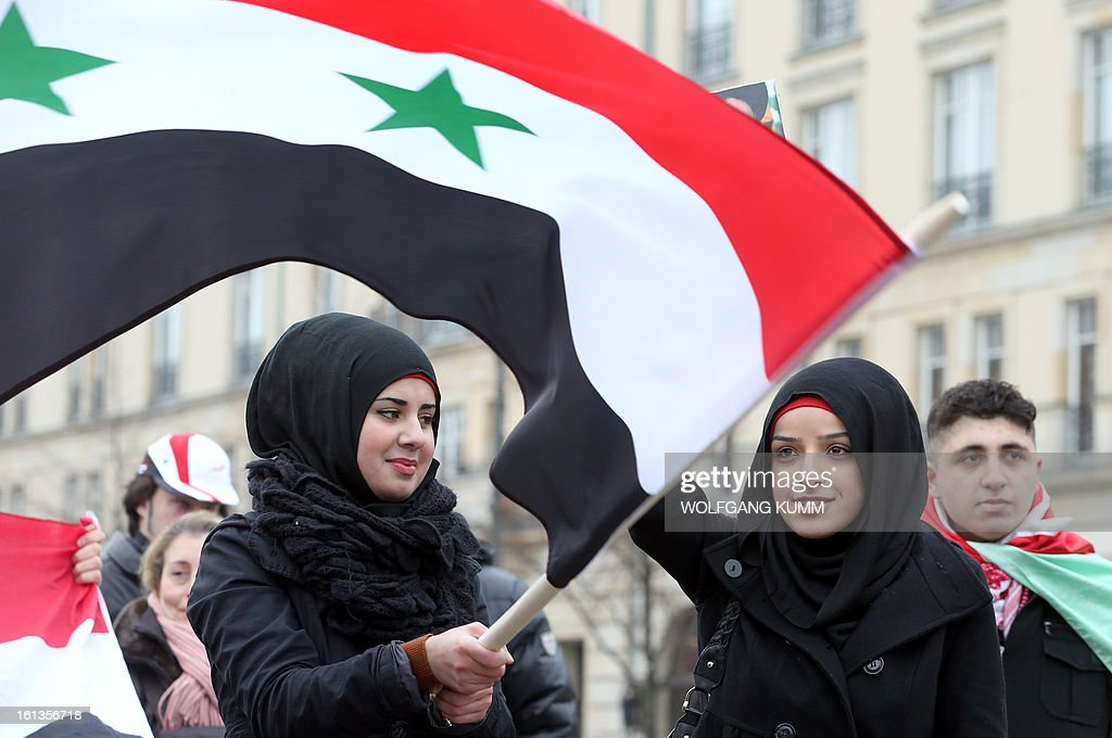 Demonstrators wave flags of Syria as they rally in front of Berlin's landmark the Brandenburg Gate to support Syrian President Bashar al-Assad's regime on February 10, 2013 in Berlin. President Bashar al-Assad reshuffled his cabinet Saturday (February 9, 2013) as regime warplanes raided rebel areas in a bid to end the stalemate in Syria's deadly civil war and hopes for a political solution appeared to founder.