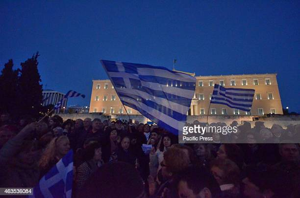 Demonstrators wave Greek flags in the air Greeks demonstrated all over Greece in support of the Greek government efforts to find a new agreement for...