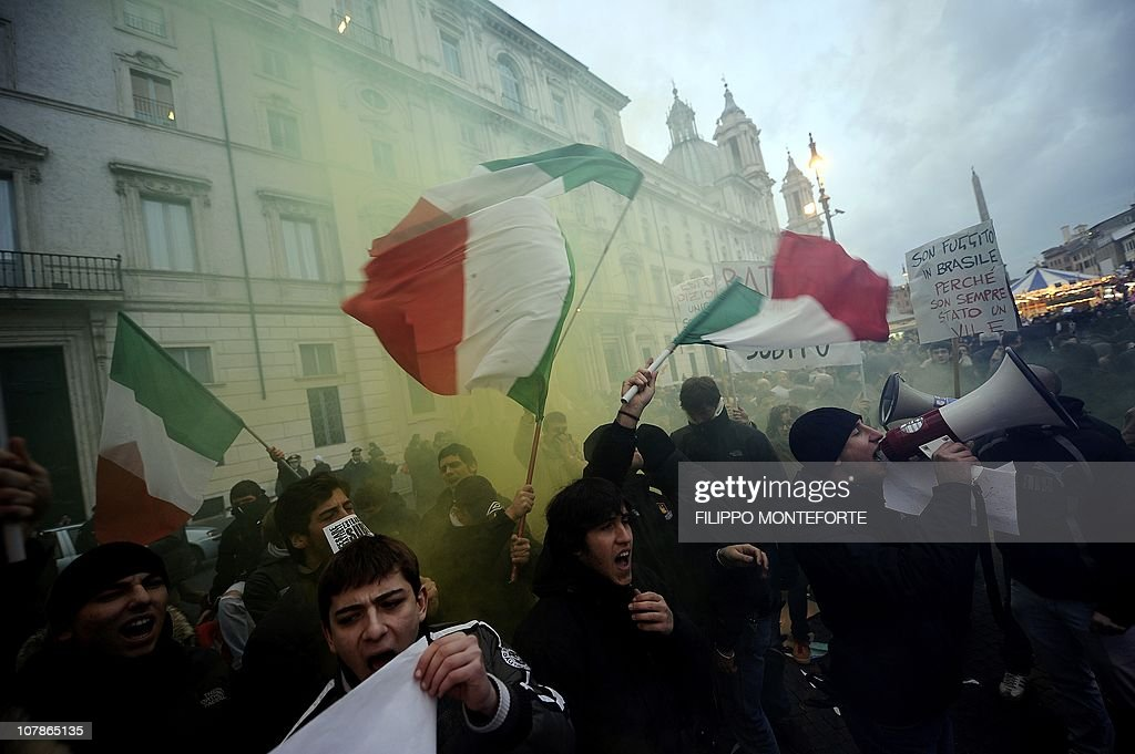 Demonstrators wave Italian flags in front of Brazil's embassy (L) to protest Brazilian President Lula's refusal to extradite ex-militant Cesare Battisti on January 4, 2011 at Piazza Navona in Rome. President Luiz Inacio Lula da Silva's refusal on December 31 to extradite Battisti, a member of the Armed Proletariat for Communism (PAC), a radical and armed left-wing group that killed several people in the 1970s, sparked a wave of indignation across Italy. Battisti has been found guilty of the group's 1978-1979 murders of a prison guard, a special investigator of terrorist organisations, a butcher and a jeweller, and in 1993 was sentenced in his absence to life in prison.