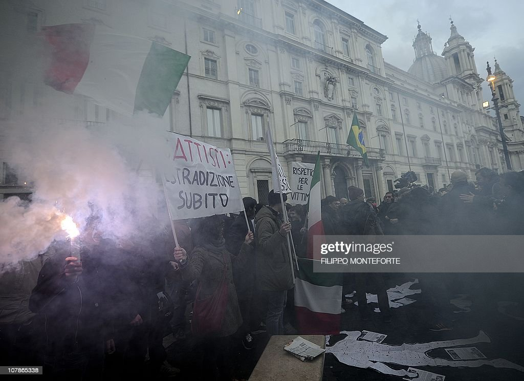 Demonstrators wave Italian flags in front of Brazil's embassy to protest Brazilian President Lula's refusal to extradite ex-militant Cesare Battisti on January 4, 2011 at Piazza Navona in Rome. President Luiz Inacio Lula da Silva's refusal on December 31 to extradite Battisti, a member of the Armed Proletariat for Communism (PAC), a radical and armed left-wing group that killed several people in the 1970s, sparked a wave of indignation across Italy. Battisti has been found guilty of the group's 1978-1979 murders of a prison guard, a special investigator of terrorist organisations, a butcher and a jeweller, and in 1993 was sentenced in his absence to life in prison.