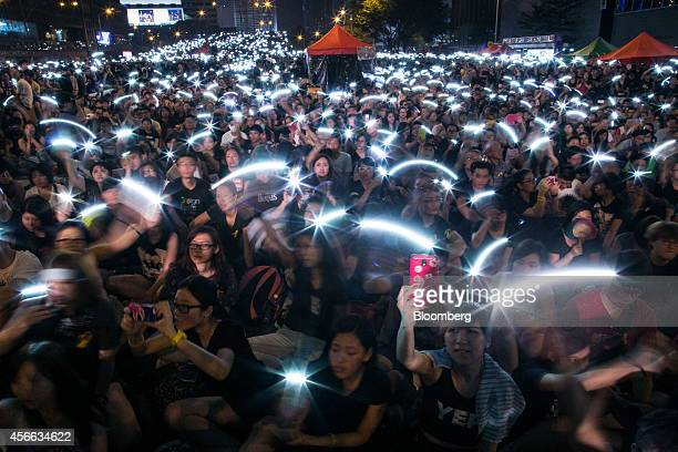 Demonstrators wave lights from their mobile devices during an ongoing protest outside central government offices in Hong Kong China on Saturday Oct 4...