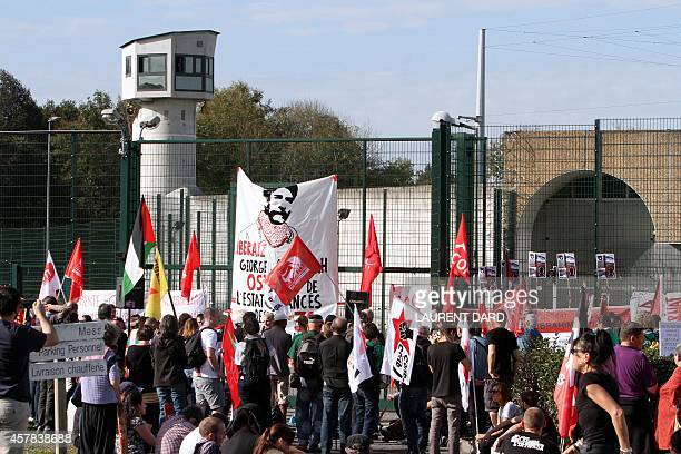 Demonstrators wave Palestinian and various Communist organisation flags as they gather in front of the prison in Lannemezan southern France on...
