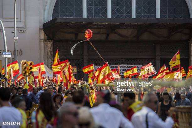 Demonstrators wave Spanish national flags and Catalan flags also known as the Senyera during a protest for Spanish unity outside of the Estacion de...