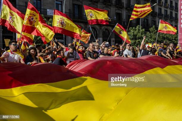 Demonstrators wave Spanish national flags and Catalan flags also known as the Senyera during a protest for Spanish unity on the Marqus de la...