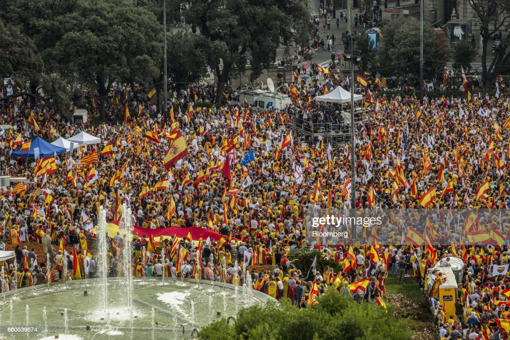 Demonstrators wave Spanish national flags as they gather on Catalonia Square in support of Spanish unity during a march on Spain's National Day in Barcelona, Spain, on Thursday, Oct. 12, 2017. Prime MinisterMariano Rajoygave his Catalan antagonist Carles Puigdemont five days to clarify whether he has declared independence from Spain or not as the country prepared for its national holiday on Thursday. Photographer: Angel Garcia/Bloomberg via Getty Images
