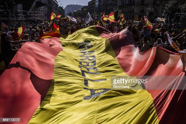 Demonstrators wave Spanish national flags during a protest for Spanish unity on the Marqus de la Argentera Avenue in Barcelona Spain on Sunday Oct 8...