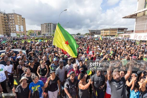 TOPSHOT Demonstrators wave the flag of French Guiana during a march in support of the general strike in Cayenne on the French overseas territory of...