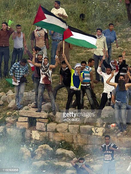 JG1053 Demonstrators wave the Palestinian flag as the Israeli army fire teargas as they gather along Syria's border with Israel while trying to cut...