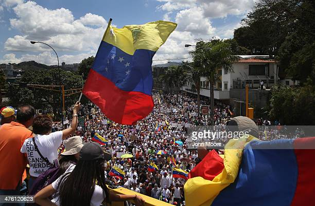 Demonstrators wave Venezuelan flags as thousands of antigovernment protesters march on March 2 2014 in Caracas Venezuela Venezuela has one of the...
