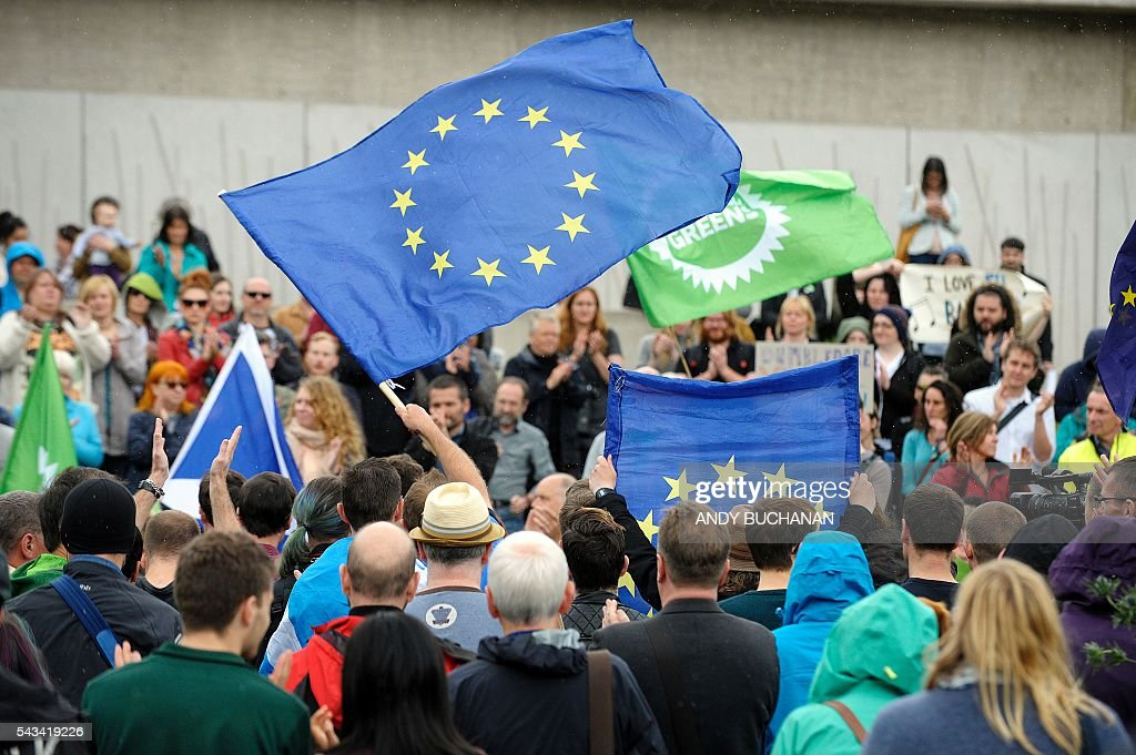 Demonstrators waves EU flags at a protest by Pro EU campaigners outside the Scottish Parliament ahead of a debate on the EU Referendum result and the implications for Scotland, in Edinburgh, Scotland on June 28, 2016. Scottish First Minister Nicola Sturgeon said she would travel to Brussels on Wednesday for talks to defend Scotland's place in the European Union after a vote by Britain as a whole to leave the bloc. Sturgeon said she was 'utterly determined' to protect Scotland as she asked an emergency session of the Scottish parliament on Tuesday for a formal mandate for direct talks with the European Union institutions. / AFP / Andy Buchanan