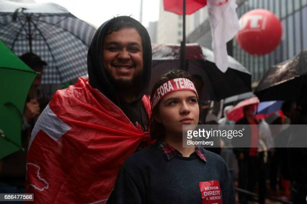 Demonstrators wear a flag and headband that reads 'Temer Out' during a protest against Brazilian President Michel Temer and a demand for new...