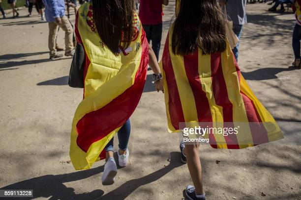 Demonstrators wear a Spanish national flag and a Catalan flag also known as the Senyera during a protest for Spanish unity in the Ciutadella Park in...