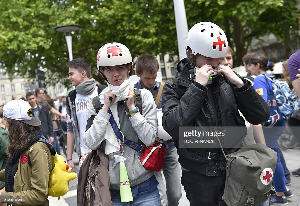 Demonstrators wear first aid helmets and kits during a protest against controversial labour reforms, on June 28, 2016 in Nantes, western France. People took to the streets in France on June 28 in the latest protest march in a marathon campaign against the French Socialist government's job market reforms. Last month the government used a constitutional manoeuvre to push the bill through the lower house without a vote in the face of opposition from Socialist backbenchers. / AFP / LOIC
