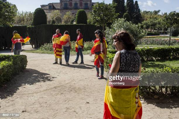 Demonstrators wear Spanish national flags and Catalan flags also known as the Senyera during a protest for Spanish unity outside of the Catalan...