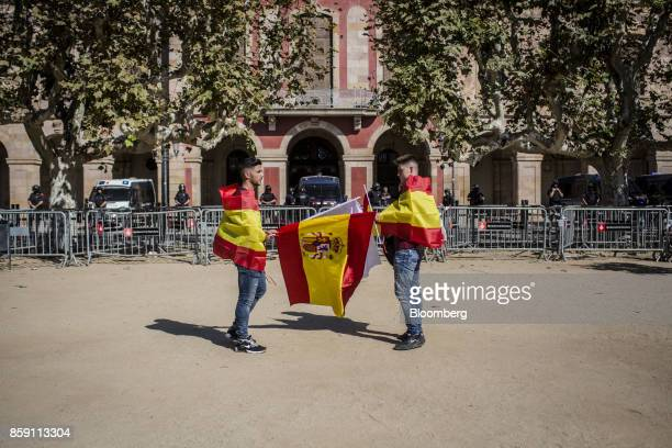 Demonstrators wear Spanish national flags during a protest for Spanish unity outside of the Catalan Parliament in Barcelona Spain on Sunday Oct 8...