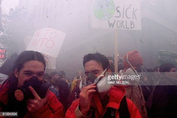 Demonstrators wearing gas masks protect themselves from tear gas during street clashes with riot police in downtown Seattle Washington on the opening...