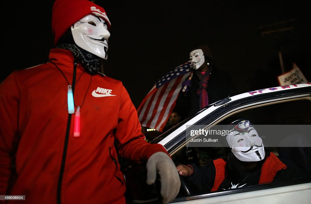 Demonstrators wearing Guy Fawkes masks as they block traffic during a protest in front of the Ferguson police department on November 24, 2014 in Ferguson, Missouri. A St. Louis County grand jury has reached a decision on whether or not to charge Ferguson police Officer Darren Wilson in the shooting of Michael Brown that sparked riots in Ferguson, Missouri in August.