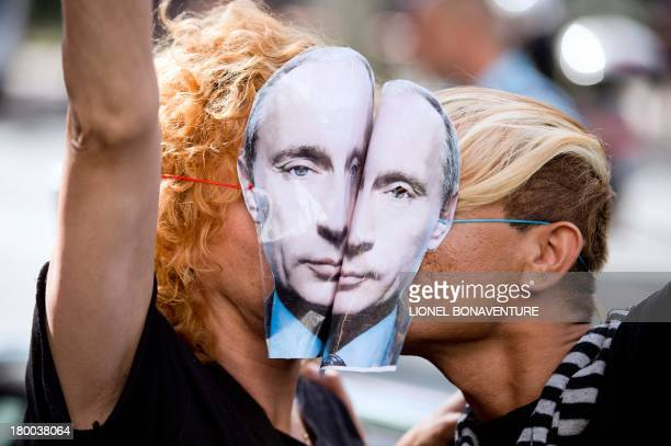 Demonstrators wearing masks depicting Russian President Vladimir Putin kiss as they take part in a rally in front of the Russian embassy in Paris on...