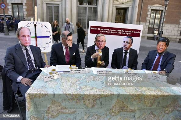 TOPSHOT Demonstrators wearing masks depicting Russian President Vladimir Putin Spanish Prime Minister Mariano Rajoy President of the European...