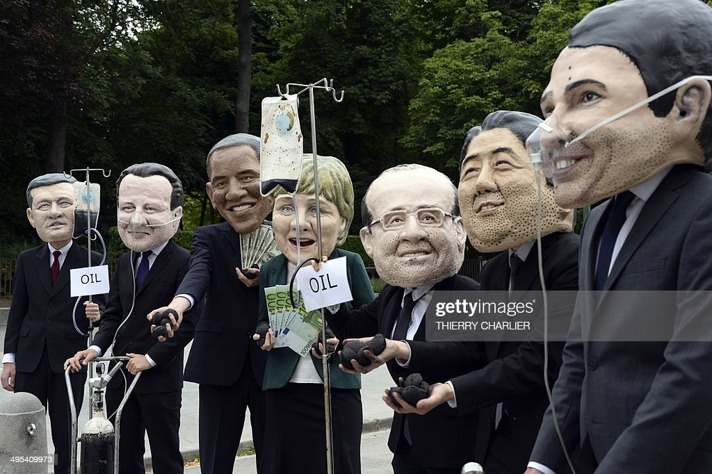 Demonstrators wearing masks of G7 leaders are hooked up to gas canisters while others are hooked up to shale gas, or are fed oil through IV tubes. They demonstrate to highlight how the G7 remains hooked on dirty energy in the Cinquantenaire Parc in Brussels,on June 3, 2014, ahead of a two day G7 meeting in Brussels on June 4-5 . AFP Photo/Thierry Charlier