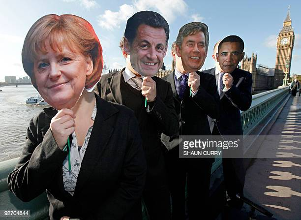 Demonstrators wearing masks representing German Chancellor Angela Merkel French President Nicolas Sarkozy British Prime Minister Gordon Brown and US...