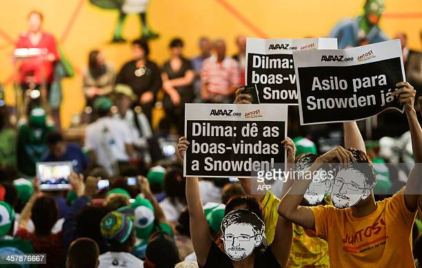 Demonstrators wearing masks with the face of Edward Snowden take part in a demonstration asking Brazilian President Dilma Rousseff to grant him...