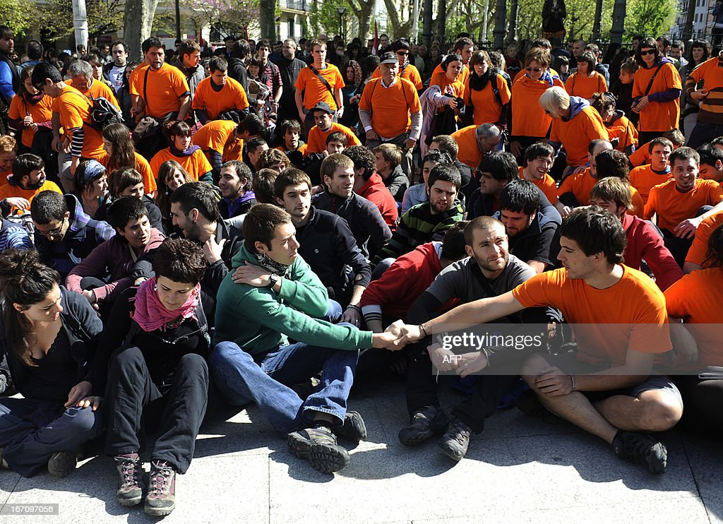 Demonstrators wearing orange shirts surround alleged members of various Basque pro-independence organizations, some of whom are facing trials, during a protest against the arrest of eight members of the Basque pro-independence youth organization SEGI in the northern Spanish Basque city of San Sebastian on April 20, 2013. Hundreds of people took part in a march from the 'Askegunea' square, where six members of SEGI were arrested on April 19, to Martutene's prison in San Sebastian. Spain's supreme court sentenced SEGI's members Mikel Arretxe, Imanol Vicente, Naikari Otaegi, Egoi Alberdi, Aitor Olaizola, Adur Fernandez, Oier Lorente y Ekaitz Ezkerra to six years in jail on April 8 for membership in an organized armed group. AFP PHOTO / ANDER GILLENEA