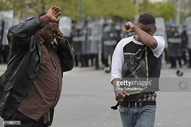 Demonstrators wipe pepper spray out of their eyes near the Mondawmin Mall during violent protests following the funeral of Freddie Gray April 27 2015...