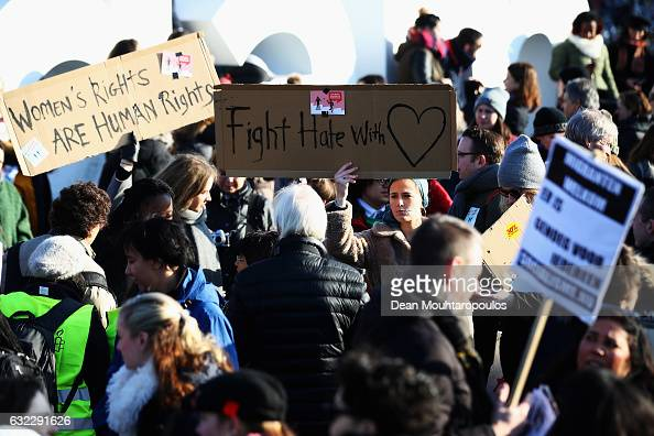 Demonstrators with a sign saying ' Women's rights are human rights and Fight Hate with Love ' make their way from the iamsterdam statue in front of...