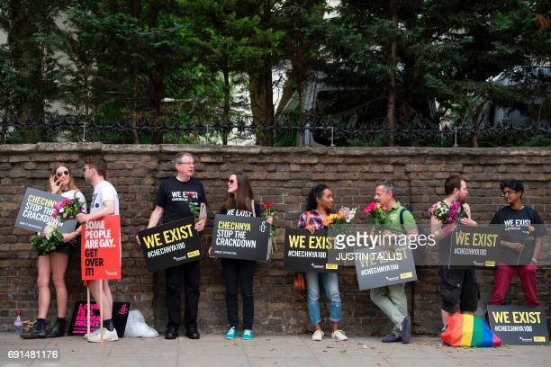 Demonstrators with placards line a wall as they protest over an alleged crackdown on gay men in Chechnya outside the Russian Embassy in London on...