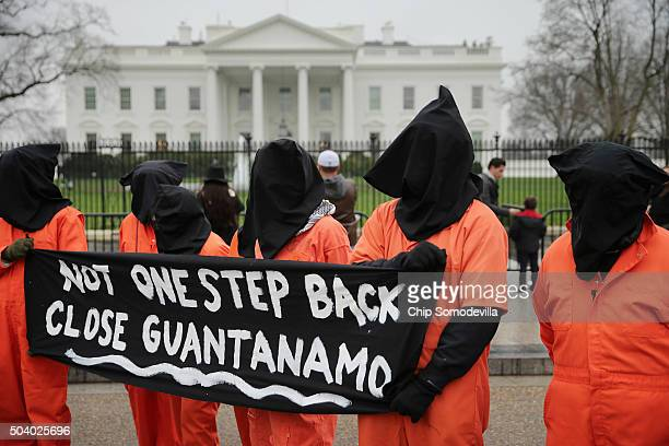 Demonstrators with the group Witness Against Torture dress in orange jumpsuits and wear black hoods while demanding that US President Barack Obama...