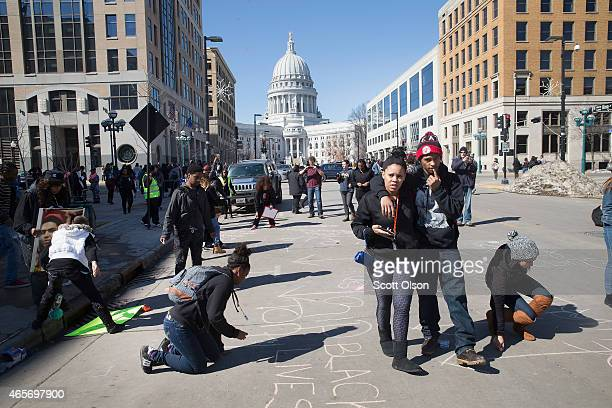 Demonstrators write messages on the street in front of the City Hall building on March 9 2015 in Madison Wisconsin The demonstrators were angry about...