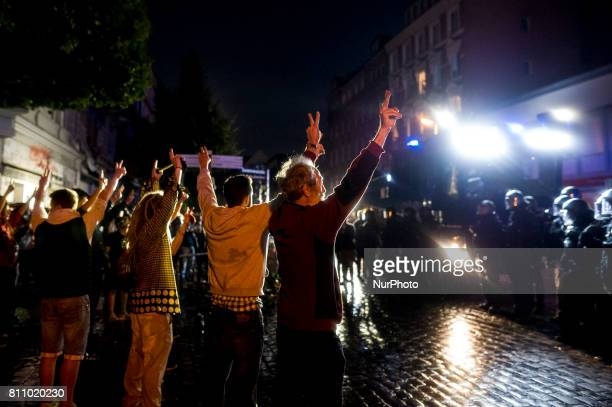 Demonstratorsbuild a row in front of a water cannon and shout quotPeace Peacequot in Hamburg on July 8 2017 Aer the police had cleared a lot of...