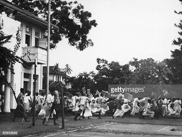Demontrators flee the grounds of India House in Columbo Sri Lanka as their demonstration against the Indian government's imposition of presidential...