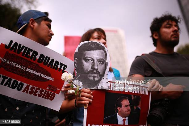 Demostrators hold banners and a portrait of Ruben Espinosa during a protest to demand the clarification of the murder of photojournalist Ruben...