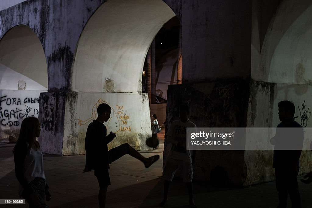 Demostrators play football under the arches of the former Lapa aqueduct during a silent demonstration against police violence against protestors, political corruption and demanding better public services in Rio de Janeiro, Brazil, on October 31, 2013.