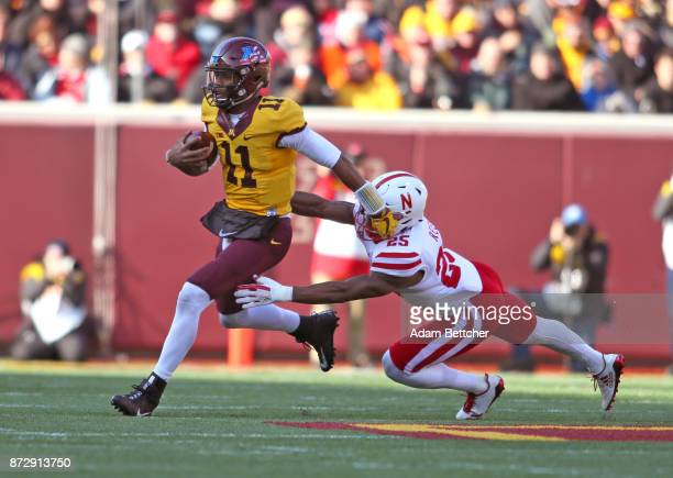 Demry Croft of the Minnesota Golden Gophers carries the ball for a gain while Antonio Reed attempts the tackle in the first quarter at TCF Bank...